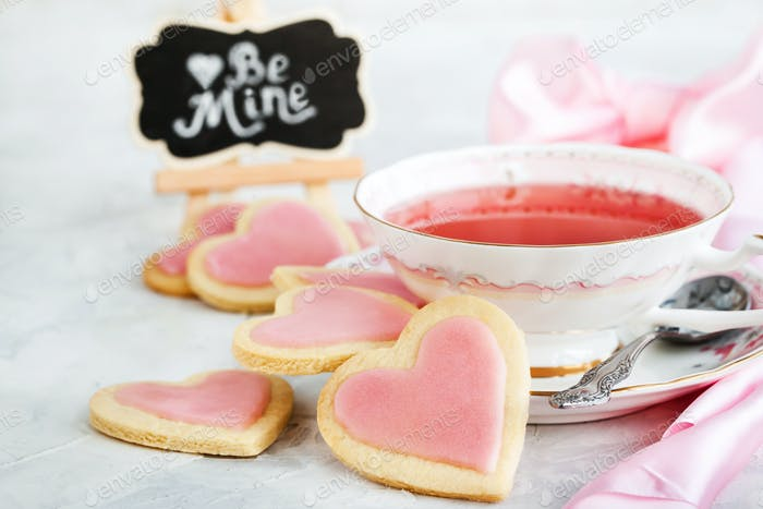 Heart shaped homemade shortbread cookies and cup of red tea, Val
