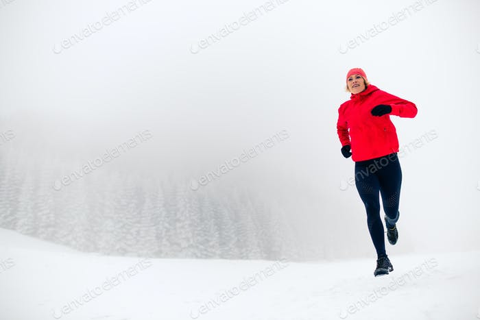 Trail running woman on snow in winter mountains