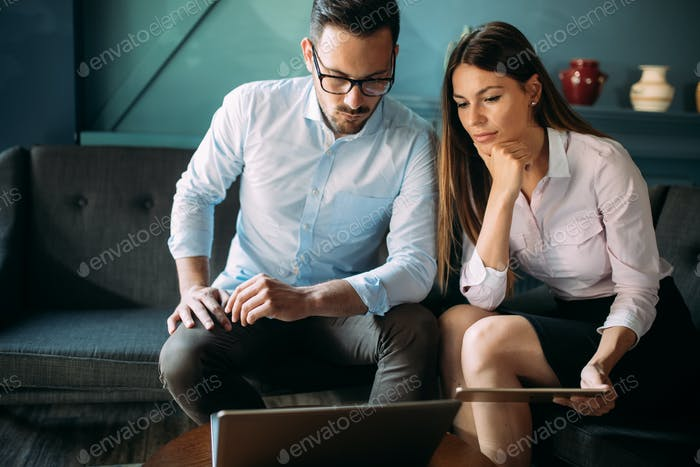 Man and woman in office working together on laptop