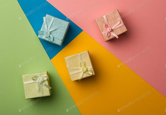 small gift boxes on multicolored paper background