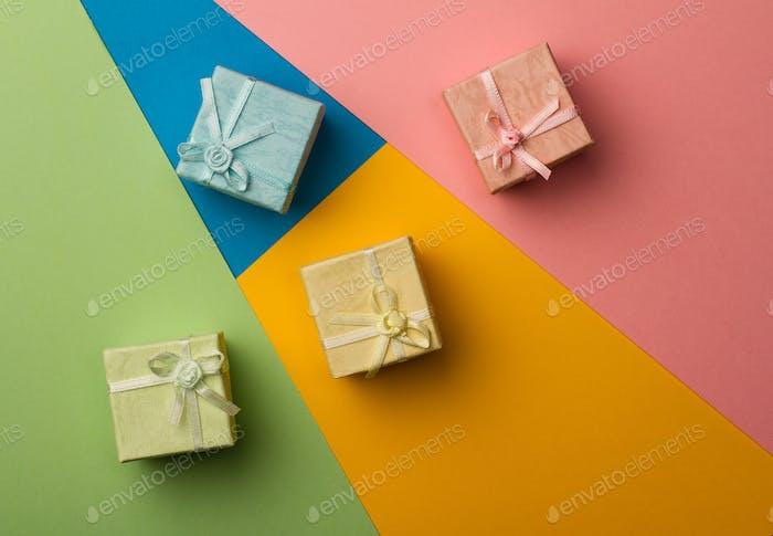 kleine Geschenkboxen auf mehrfarbigen Papierhintergrund