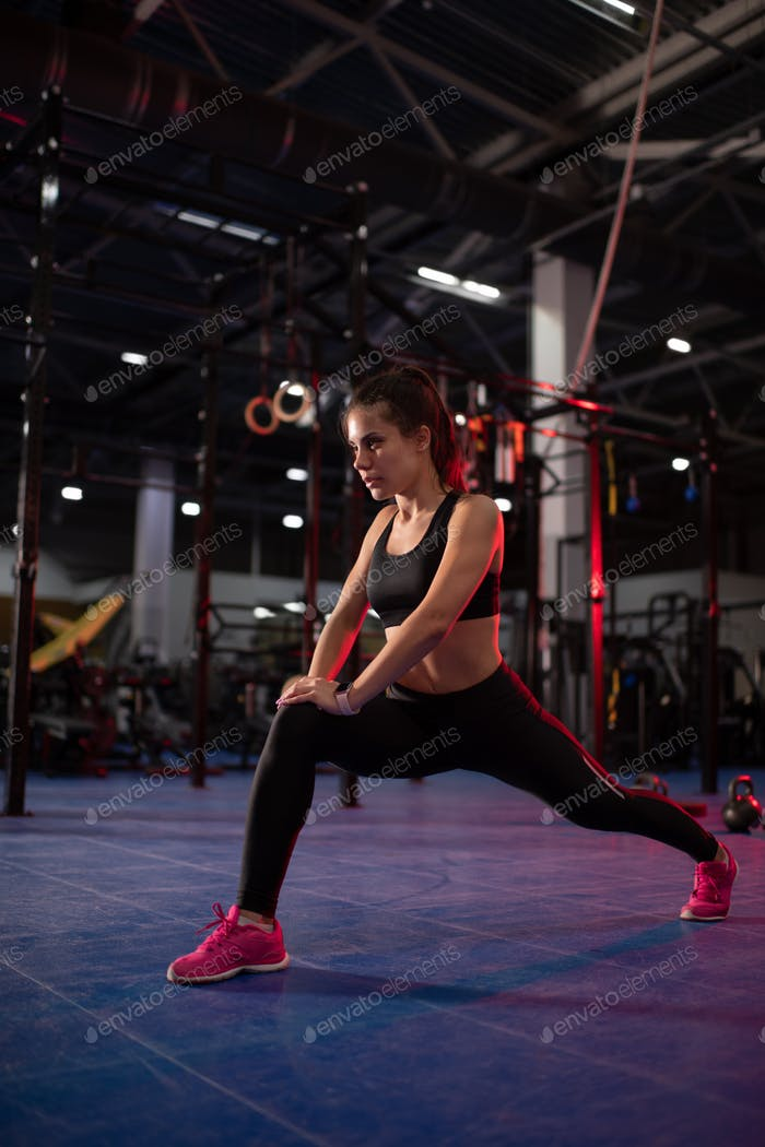 Fit sportswoman lunging in gym