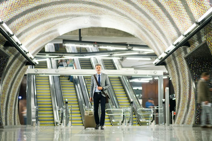 Businessman in front of escalators on a metro station.