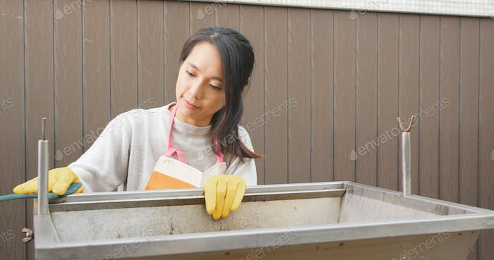 Woman cleaning barbecue stove