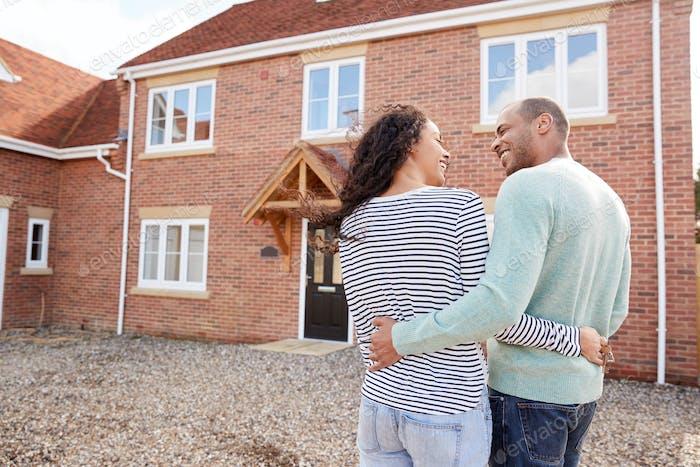Rückansicht von Paar stehend außerhalb New Home On Moving Day Blick In Haus