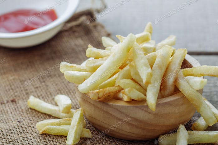 French fries and sauce on wooden