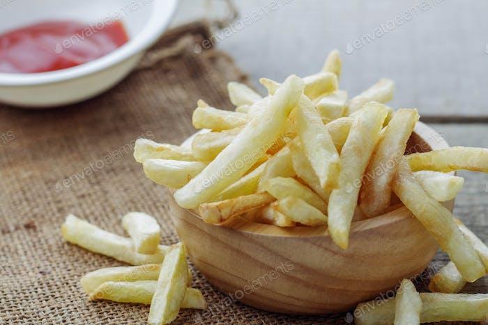 Pommes frites und Sauce auf Holz
