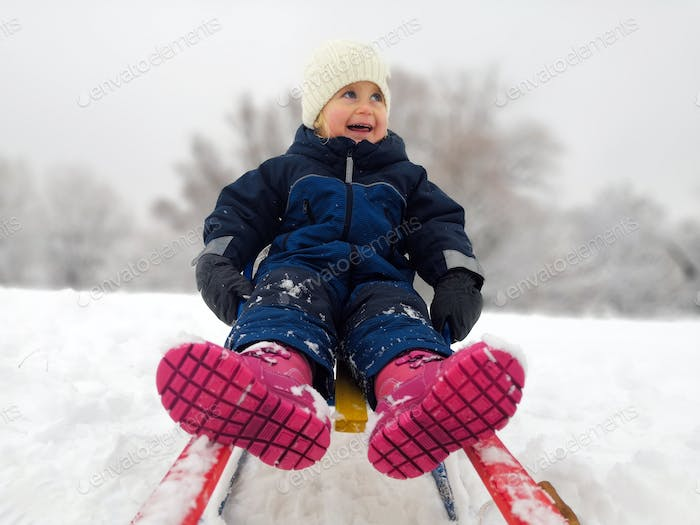 Childhood, sledding, leisure concept. Parent carrying happy little kid on sled in winter