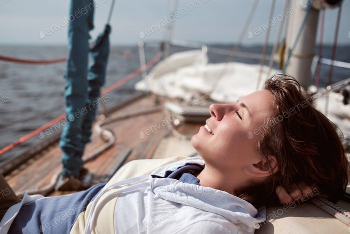 caucasian woman yachting in sea. She closes eyes and dreams