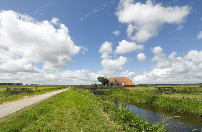 old farmhouse by river over blue sky