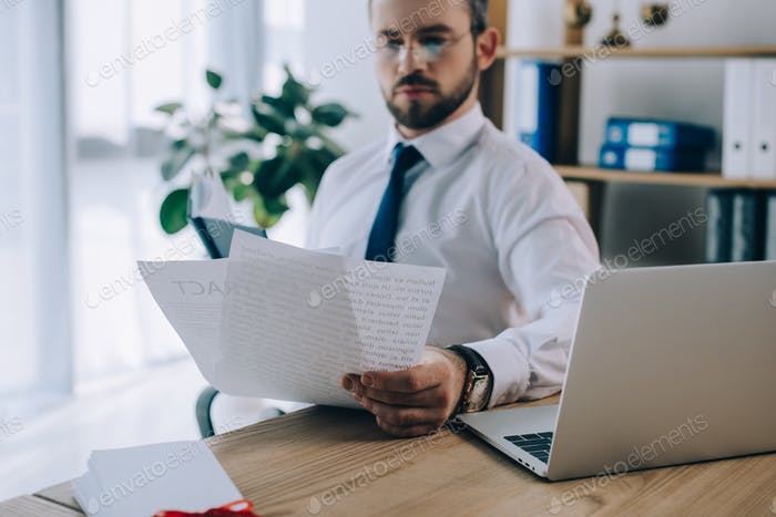 selective focus of lawyer with papers at workplace in office