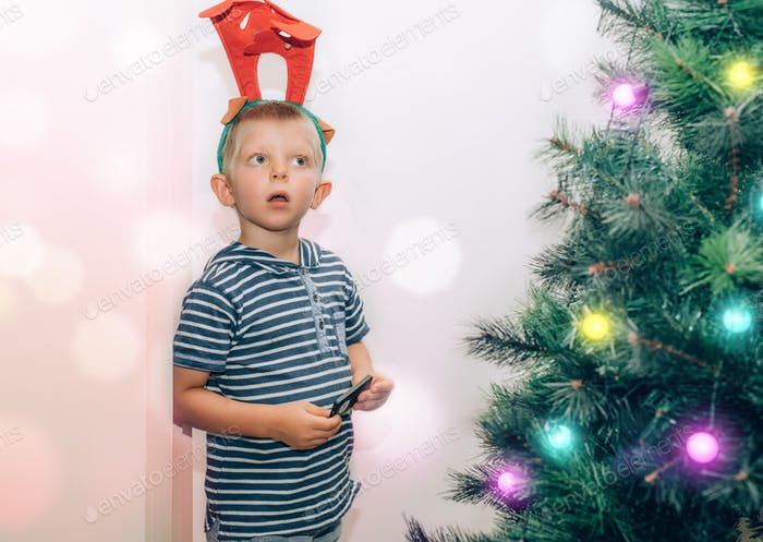 Cute little kid with deer antlers on the head playing with fairy lights on Christmas tree