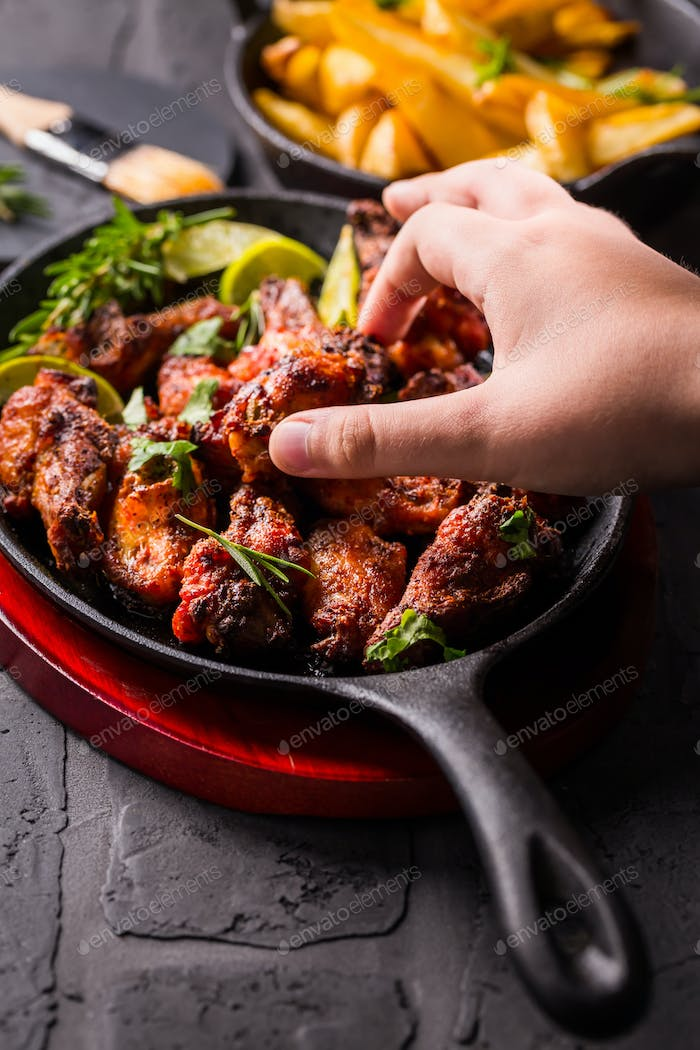 Hand swiping roasted chicken wings in barbecue sauce with lime