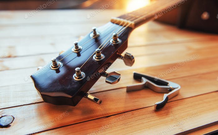 close up neck acoustic classical guitar on a light wooden background