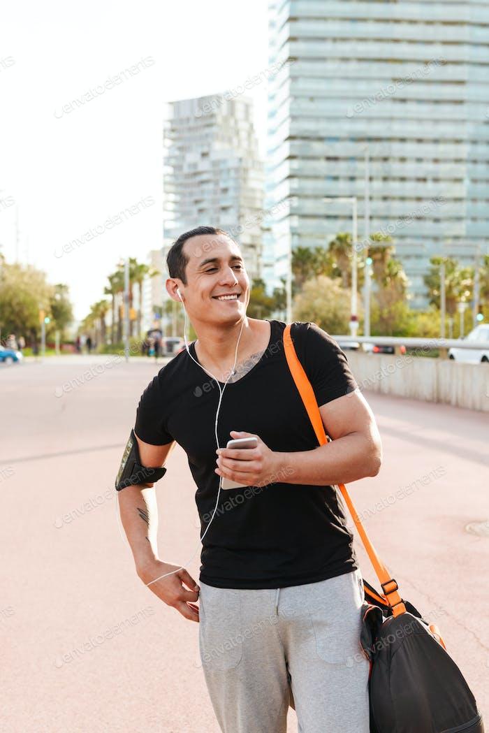 Glückliche junge starke Sport Mann im Freien zu Fuß