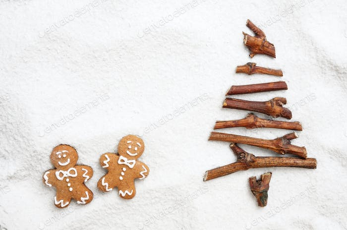 Flat lay stylized Christmas tree made of small twigs and gingerbread man cookies