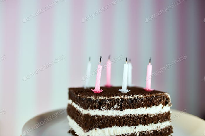 Birthday cake with burning candles on color pink background.