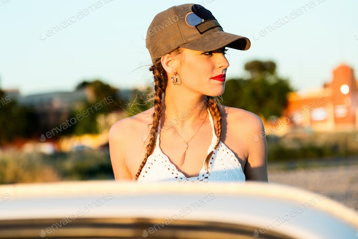Pretty young woman driving on road trip on beautiful summer day.