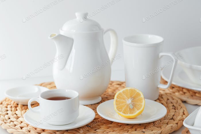 White ceramic tableware, fibre braided round placemat and cutlery set on white background.