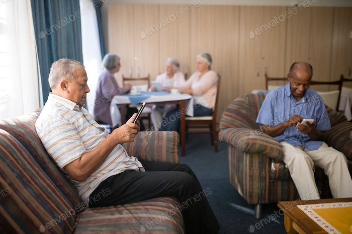 Senior men using mobile phone at nursing home
