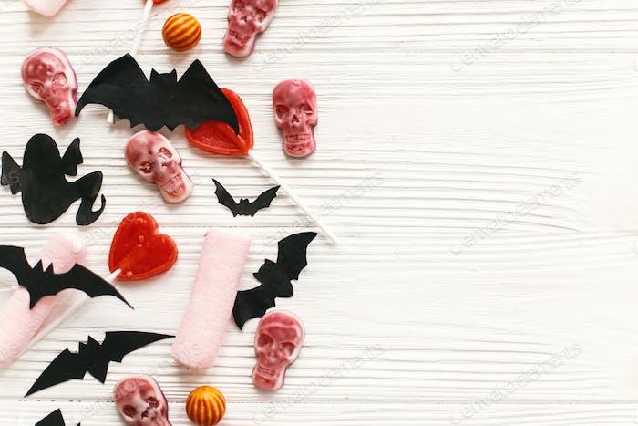 Urlaub Süßigkeiten mit Fledermäusen, Spinnen, Geister, Totenköpfe Draufsicht auf weißem rustikalem Holzhintergrund