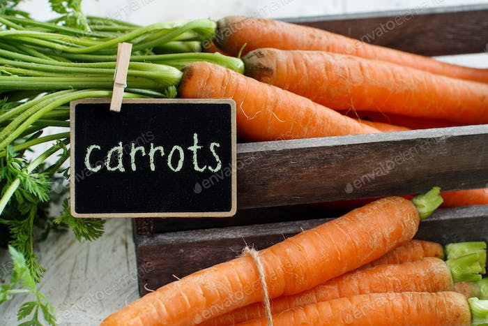 Fresh raw carrots with leaves in a box