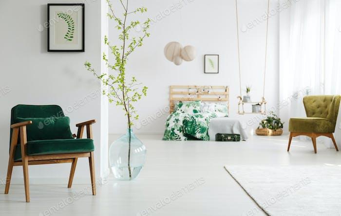 Open bedroom with green armchair