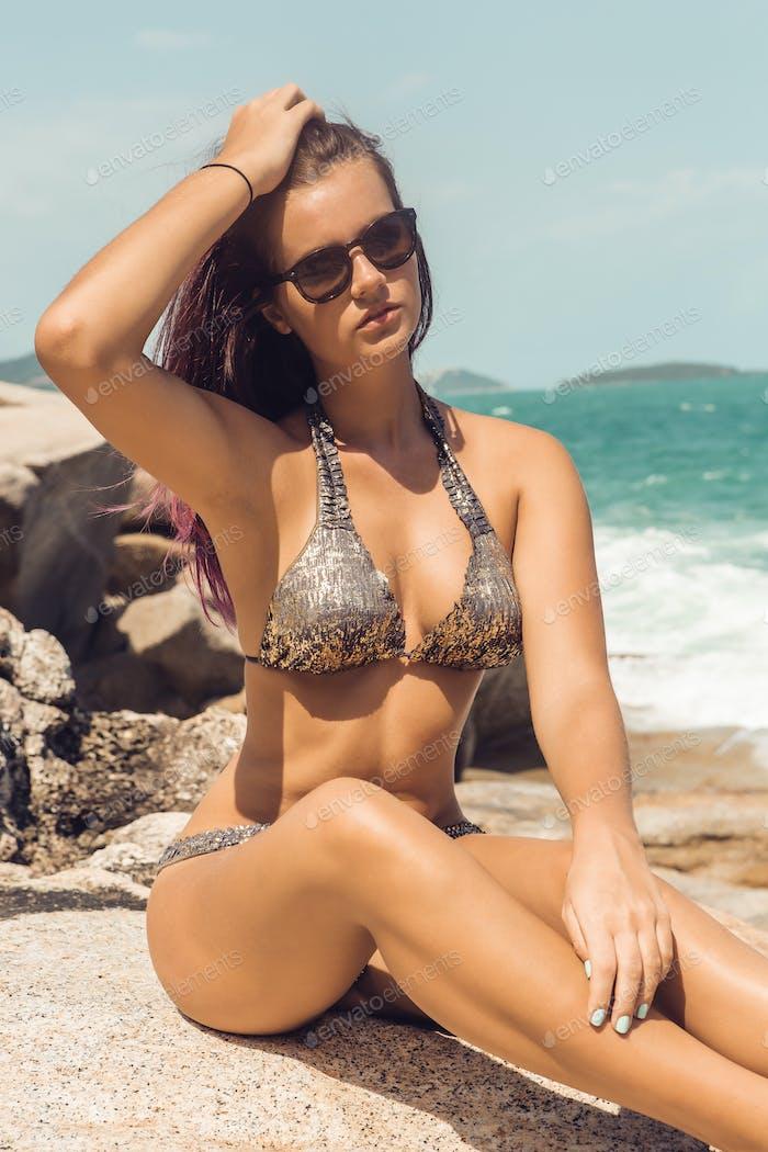Mädchen in sexy Bikini Rest am Steinstrand.