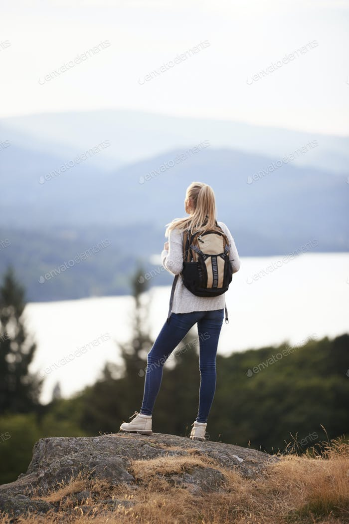 A young adult Caucasian woman standing alone on the rock after hiking, admiring lake view, back view
