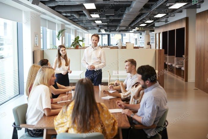Hombre de Empresario y mujer de negocios dirigiéndose al Grupo de jóvenes candidatos sentados alrededor de la mesa