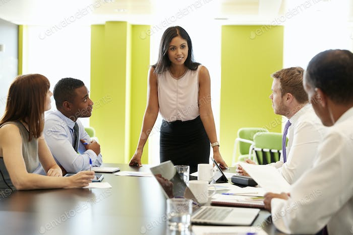 Female boss stands addressing team at informal work meeting
