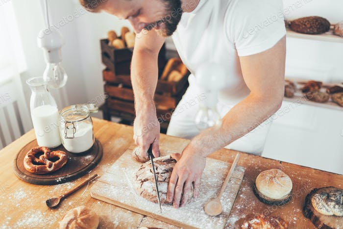 Panadero con una variedad de delicioso pan recién horneado y pastelería
