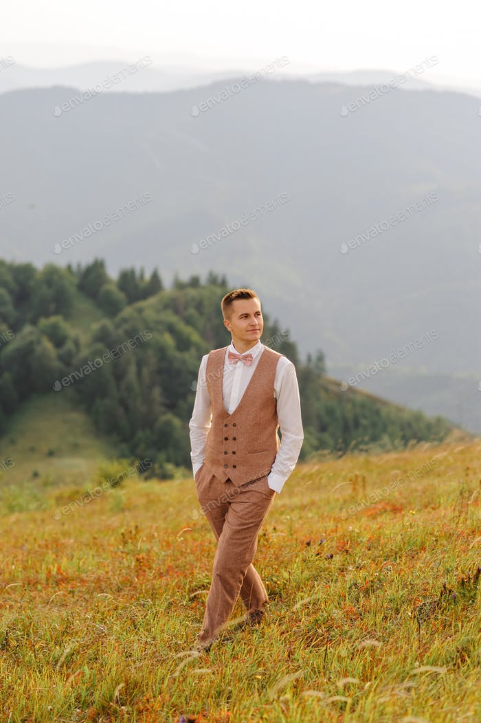 The groom is walking alone on the background of autumn mountains.