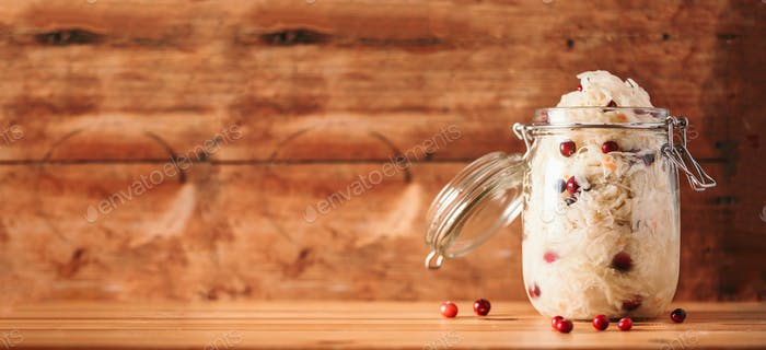 Sauerkraut in glass jar on wooden background with copy space. Fermented and marinated cabbage at