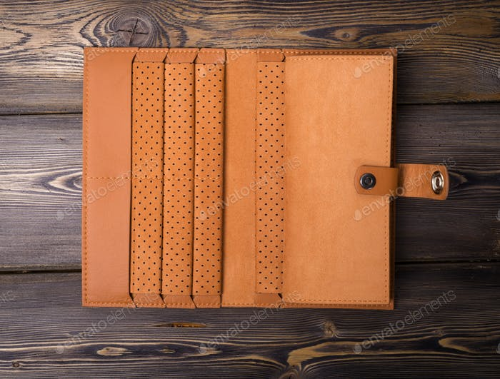 Leather wallet on the rustic wood background