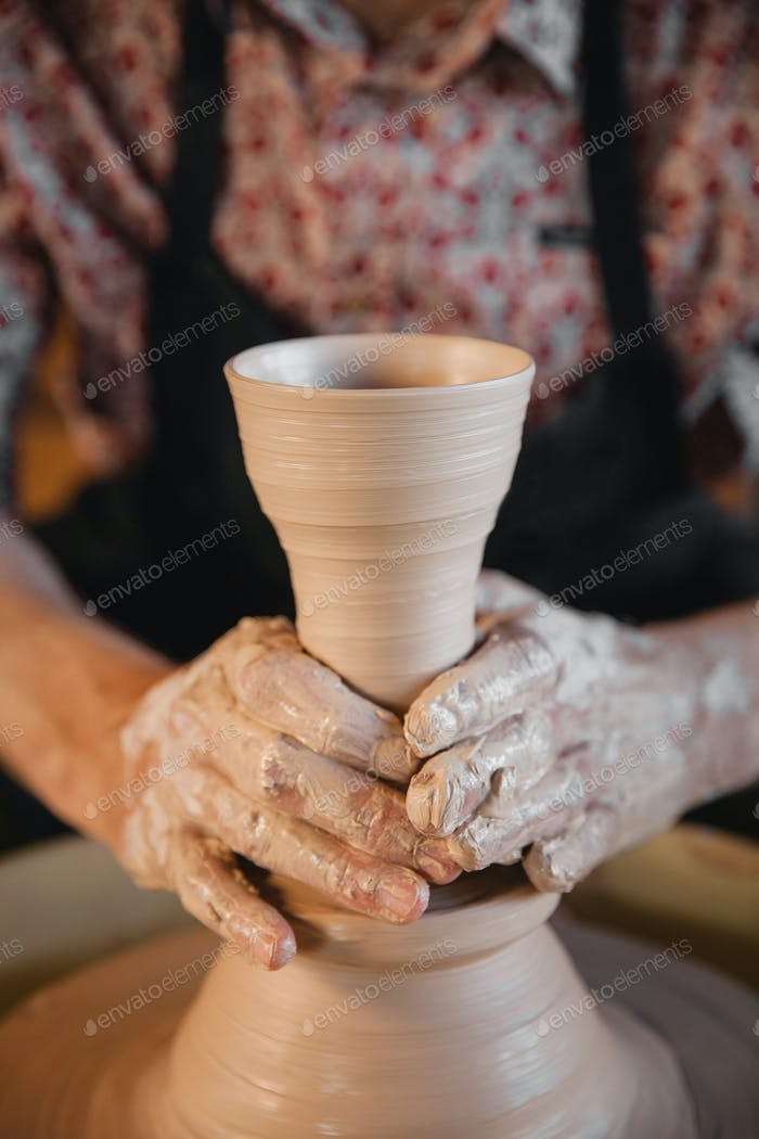 Unrecognizable potter master creating new ceramic pot