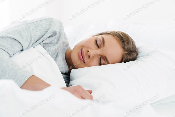 Image closeup of cute young woman lying and sleeping in bed