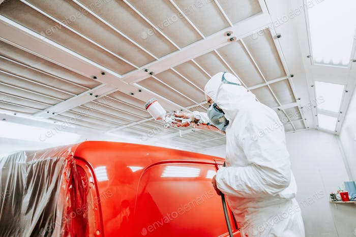 Auto mechanic painter painting a red car, a van in special booth