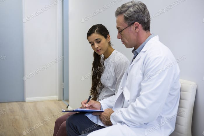 Dentist and patient discussing while sitting on sofa
