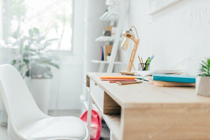 Minimalistisches Rauminterieur mit Schreibtisch und Schulbedarf auf sie platziert.