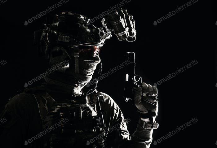 Combatant armed with service pistol in darkness