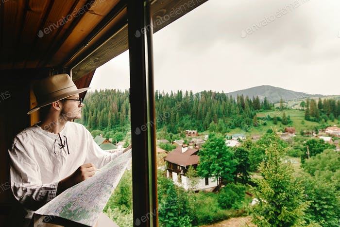 Hipster man sitting at window and holding map and exploring in wooden house