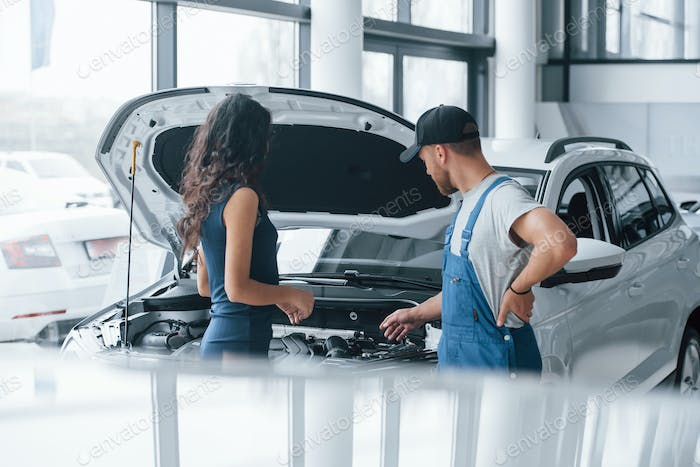 Like the new one. Woman in the auto salon with employee in blue uniform taking her repaired car back