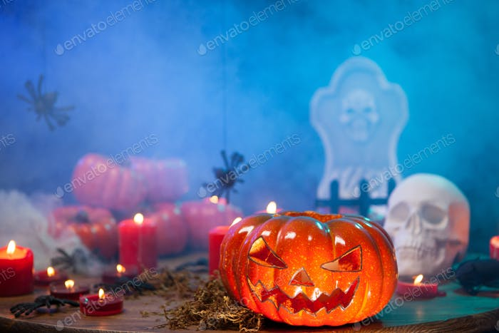 Burning candles at halloween celebration wtih creepy pumpkin near