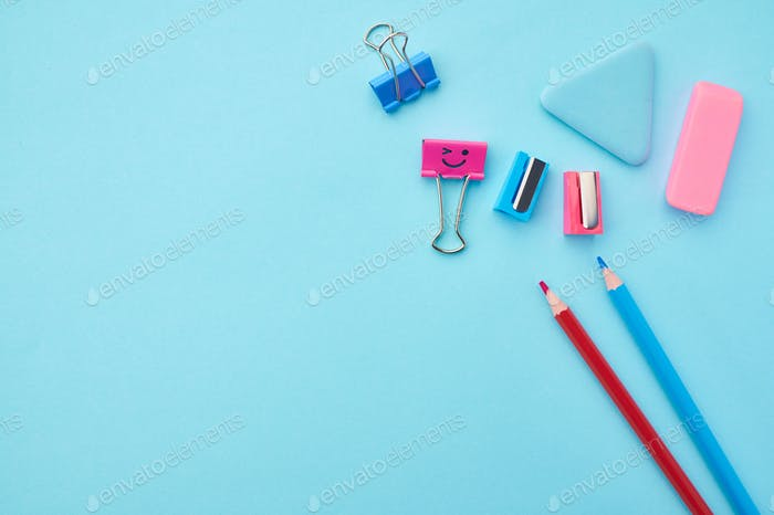 Pencils, clips and rubber on blue background