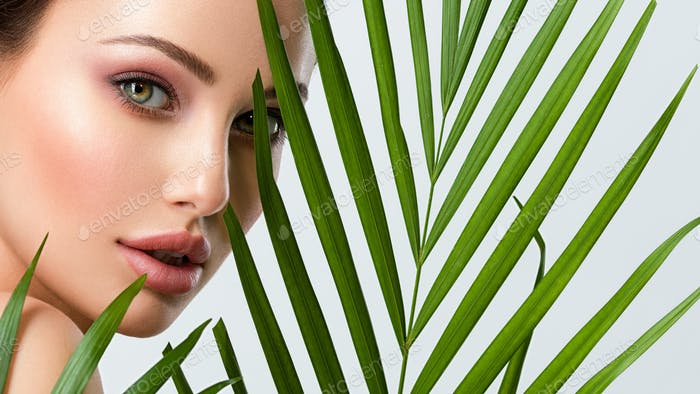 Young beautiful woman with healthy skin of face and palm leaves.