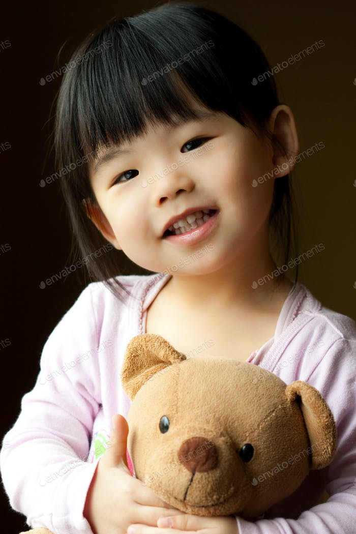 Smiling little child with a teddy bear
