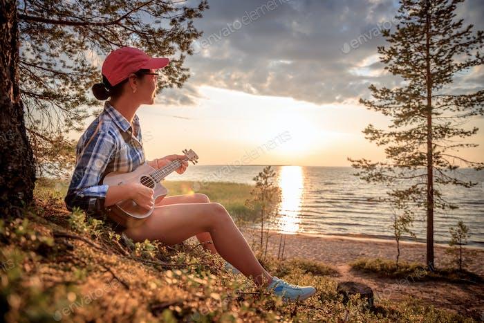 Frau bei Sonnenuntergang spielt die Ukulele
