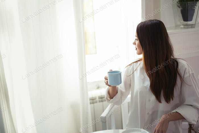 Young woman with cup of coffee sitting at table