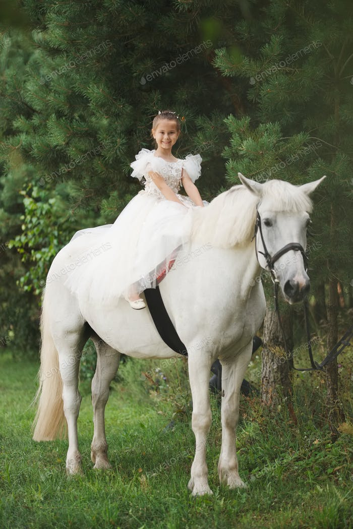 happy little princess on white horse in the forest